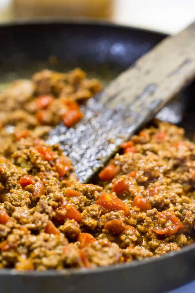 Taco Meat for Pizza browning in a skillet with a wooden spatula in the pan