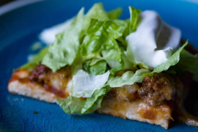 Taco pizza on blue plate with lettuce and sour cream