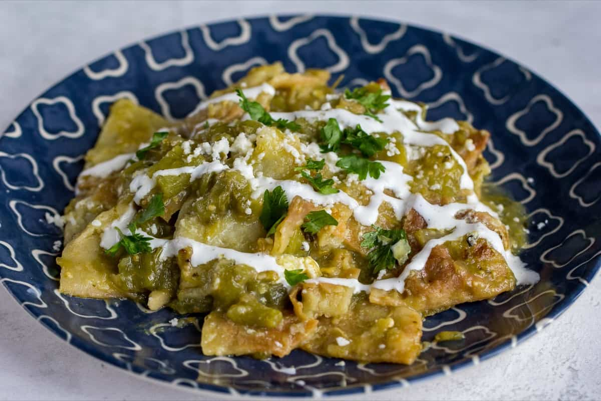 chilaquiles on a blue plate with sour cream