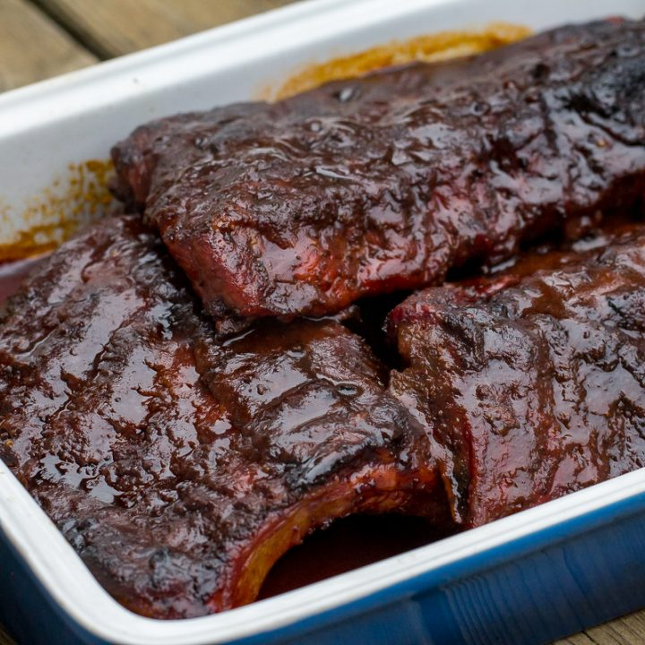 Smoked Cherry Coke Ribs in an enameled cast iron rectangle-shaped pan