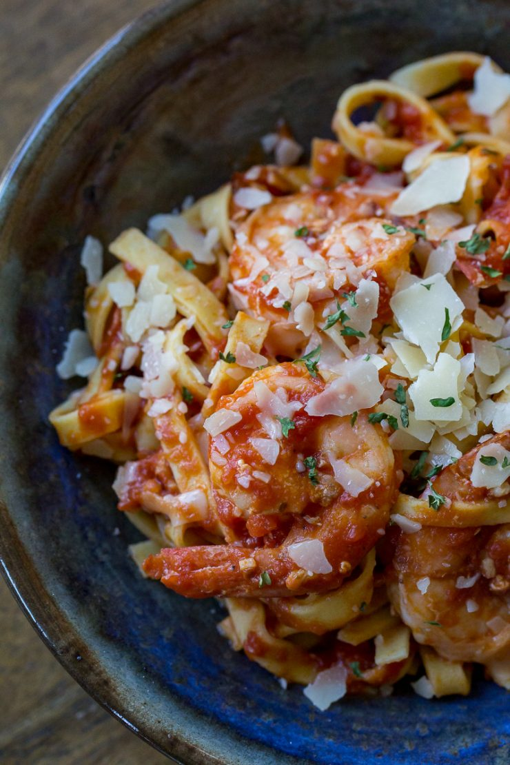 Shrimp Marinara in a blue and brown bowl with parmesan
