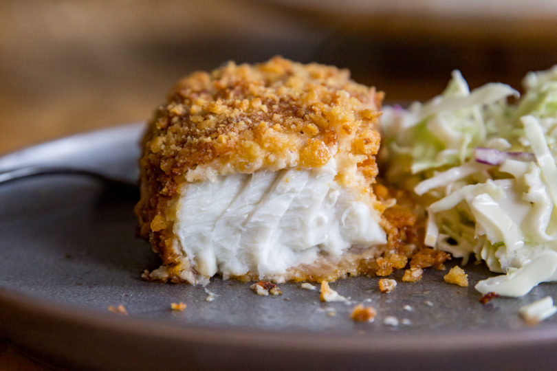 Air Fryer Parmesan Crusted Halibut on a gray plate with the flaky fish exposed