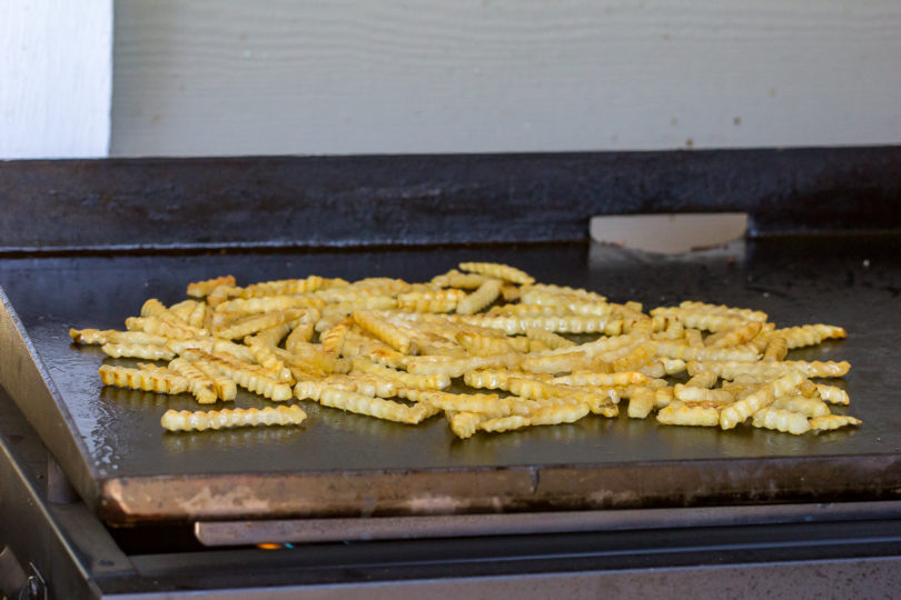 french fries cooking on a Blackstone Gas Griddle
