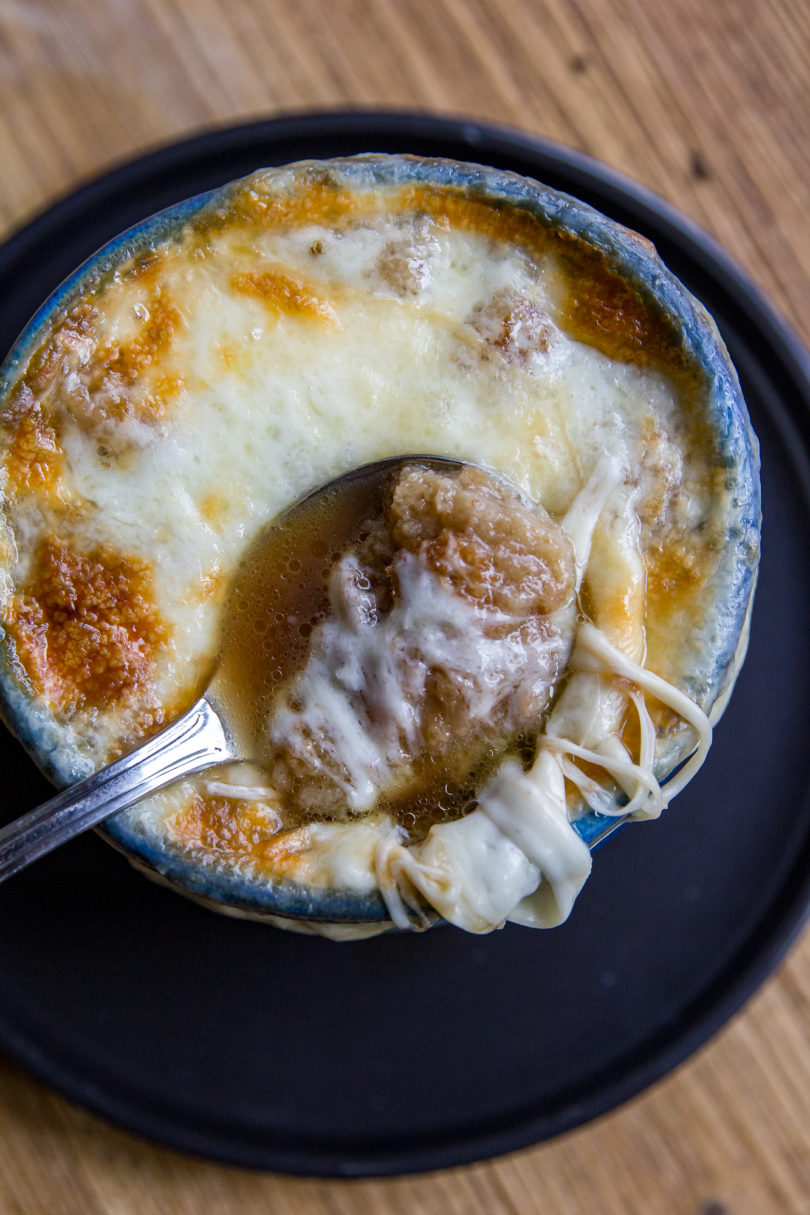 From the top view of a blue bowl of French Onion Soup with a spoon slightly sunken into the bowl on top of the cheese, and bread and cheese on a portion of the spoon.