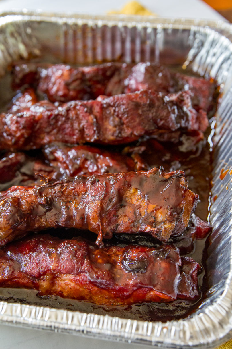 Smoked Country-Style Pork Ribs in a metal pan covered with barbecue sauce