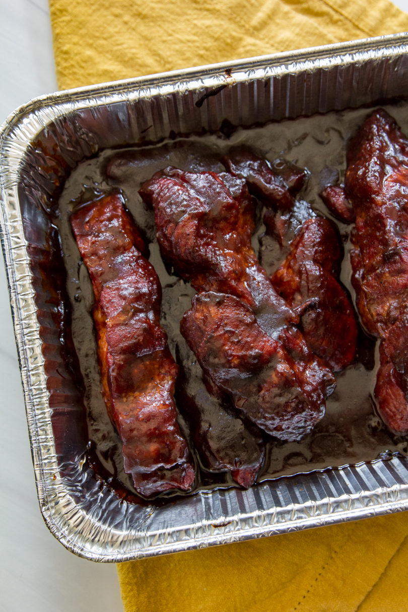 Smoked Country-Style Pork Ribs, top down view, in a foil pan with bbq sauce and the pan is placed on a yellow cloth napkin